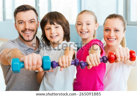 Living a healthy life together. Happy family holding different sports equipment while standing close to each other in health club  - stock photo