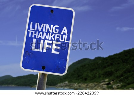 Living a Thankful Life sign with a beach on background - stock photo