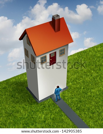 Living beyond your means with a businessman looking up at a tall house that has the entrance door too high to enter representing a financial challenge and finance confusion with real estate or money. - stock photo