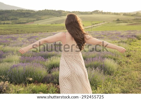 Living for the moment. Rear view of a carefree young woman standing in a lavender field, enjoying the beauty of a nature, posing with her arms outstretched. - stock photo