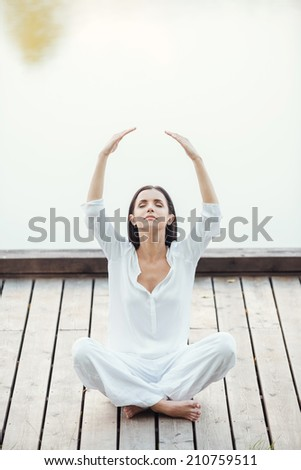 Living in balance with world. Beautiful young woman in white clothing sitting in lotus position and keeping arms raised while meditating outdoors - stock photo