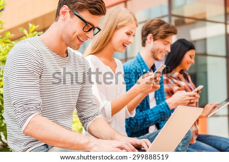 Living in digital age. Group of young people holding different digital devices and smiling while sitting in a row outdoors - stock photo