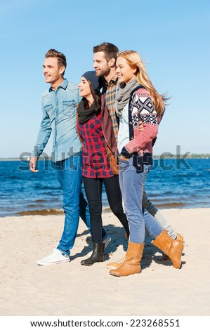 Living in the moment. Side view of four young happy people bonding to each other and smiling while walking by the beach together - stock photo