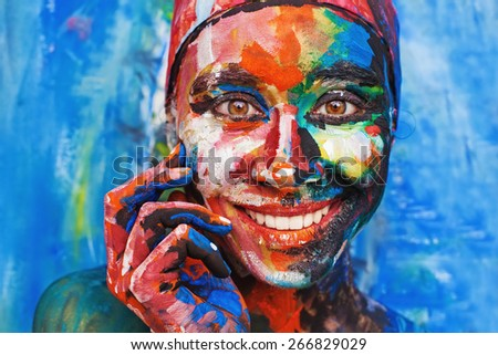 Living painting - smiling woman completely covered with thick paint - stock photo