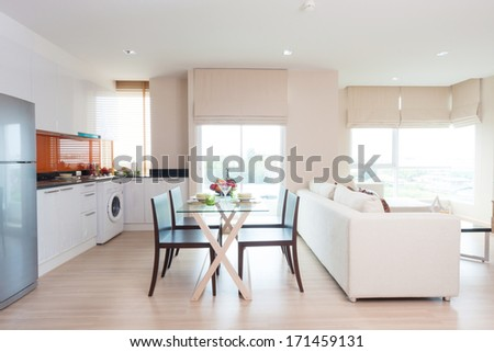 living-room and kitchen with dining table in condominium. - stock photo