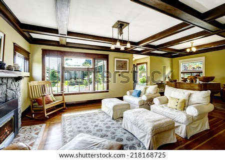 Living room design idea. Coffered ceiling, stone trim fireplace and white furniture set - stock photo