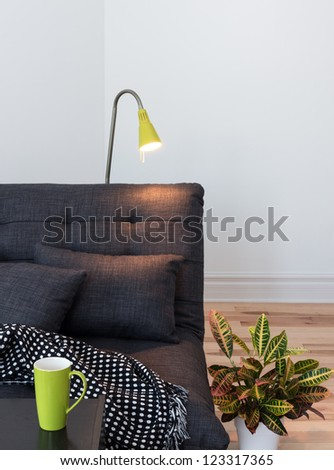 Living room detail. Cozy sofa, lamp and colorful plant. - stock photo