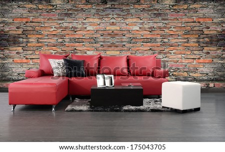 Living room. Furniture on hardwood floor against rough brick wall. - stock photo