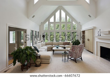 Living room in luxury home with floor to ceiling windows - stock photo
