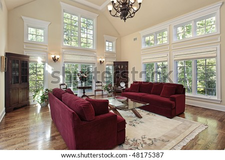 Living room in luxury home with two story windows - stock photo