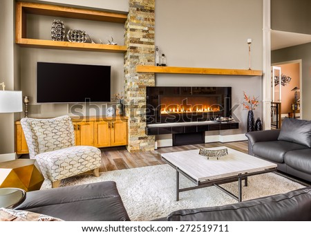 Living Room in New House:Large Furnished Living Room with Fireplace, Television, Couch, Coffee Table, and Rug - stock photo
