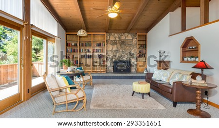 Living room interior beautifully staged with bamboo chairs, book shelf, rug and view windows. Stunning living room in craftsman home with dramatic wood beamed ceilings. Beautiful craftsman house. - stock photo