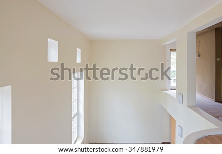 Living room interior renovation with unfinished wooden floors, big windows and balcony. - stock photo