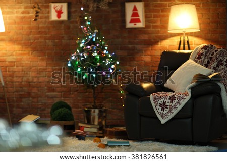 Living room interior with black armchair, lamp and Christmas tree on brick wall background