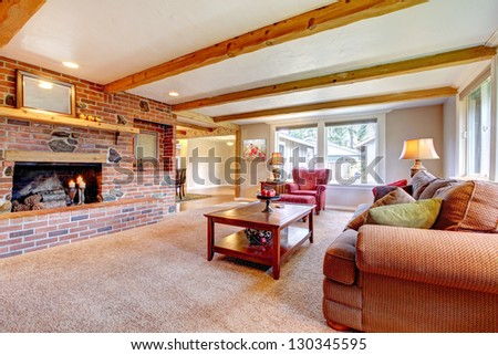 Living room interior with brick fireplace, wood beams and red. - stock photo