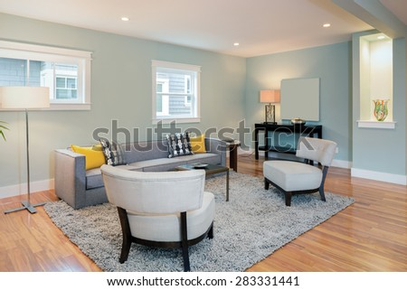 Living Room Interior with couch, chairs rug yellow pillows, lamp, wooden floor. - stock photo