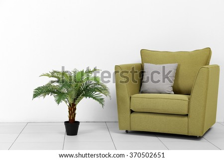 Living room interior with green armchair and plant on white wall background - stock photo