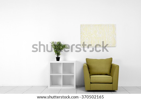 Living room interior with green armchair, white shelf and plant on white wall background - stock photo
