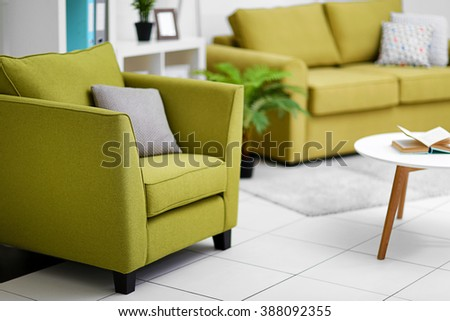 Living room interior with green furniture and table on light background - stock photo