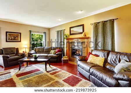 Living room interior with leather couches and colorful soft rug - stock photo