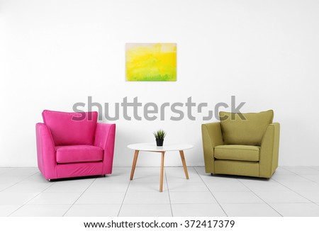 Living room interior with pink, green armchairs, white table and plant on white wall background - stock photo