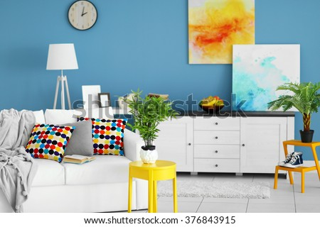 Living room interior with white furniture and green plants and pictures on blue wall background - stock photo