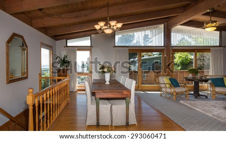 Living room interior with wooden staircase. Stunning living room in craftsman home with dining table and dramatic wood beamed ceilings. Beautiful staged living room in craftsman house. - stock photo