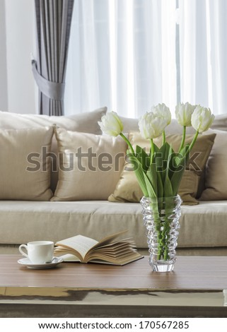 Living room sofa with coffee table book and flower - stock photo