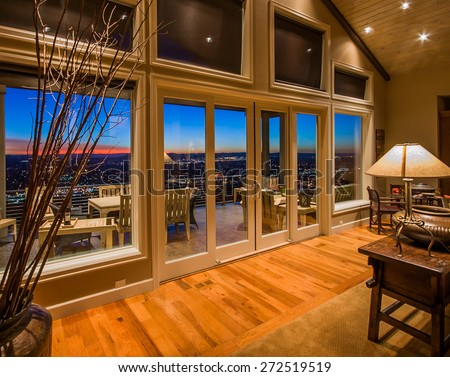 Living Room with Amazing Sunset View and Large Glass Doors and Windows in New Luxury Home - stock photo