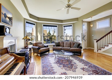 Living room with antique sofa, chair, coffee table and piano - stock photo