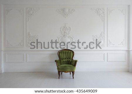 Living room with antique stylish green armchair on luxury white wall design bas-relief stucco mouldings roccoco elements - stock photo