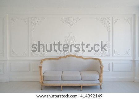 Living room with antique stylish light sofa on luxury white wall design bas-relief stucco mouldings roccoco elements  - stock photo