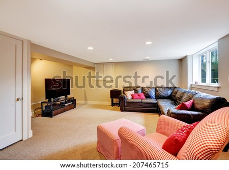 Living room with black leather couch, red chair and tv