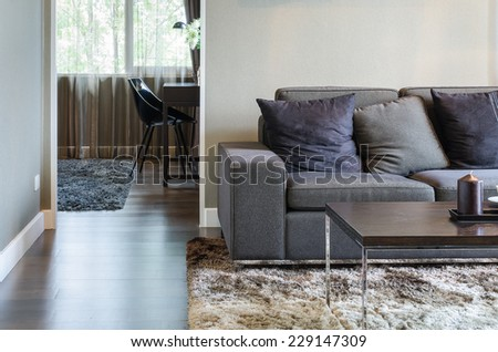 living room with black sofa and wooden table on carpet - stock photo