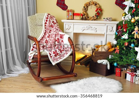 Living room with Christmas tree, fireplace and rocking chair - stock photo