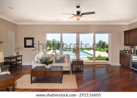 Living room with couch and kitchen and large scenic doors leading to pool. Modern villa, interior, beautiful living room - stock photo