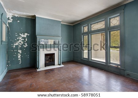 Living room with fireplace in old abandoned home - stock photo