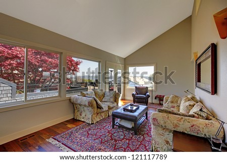 Living room with many windows, rug and two sofas.