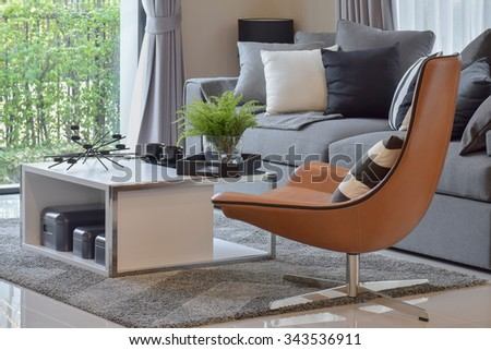 living room with plant in vase and black pattern pillows on modern leather chair - stock photo