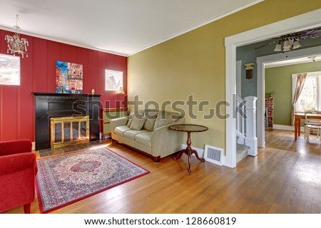 Living room with red and yellow walls and fireplace in old American house. - stock photo