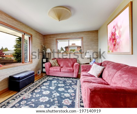 Living room with red furniture set, black ottoman and blue rug on hardwood floor