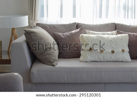 living room with row of grey pillows on sofa at home