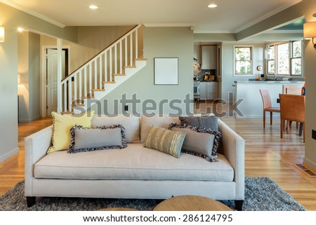 Living room with staircase, couch and kitchen. Living room interior with copy space for art with hand-woven natural colored fine sisal rug open space living room within nature. - stock photo