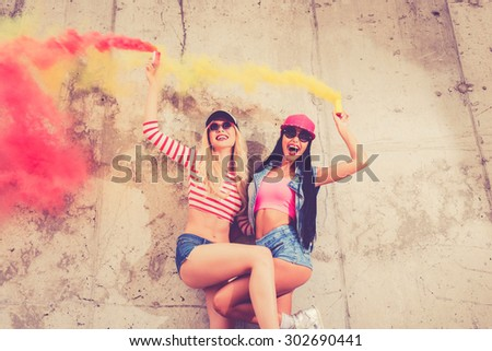 Living the bright lives. Low angle view of two cheerful young women holding smoke bombs and smiling while posing against the concrete wall - stock photo