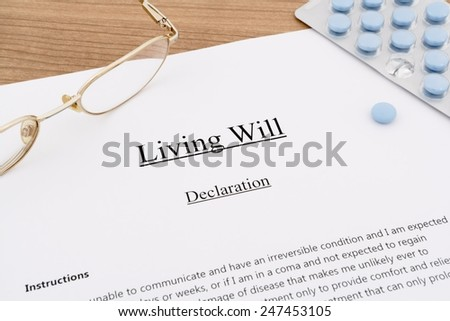 living will with pills and eyeglasses on wooden table - stock photo
