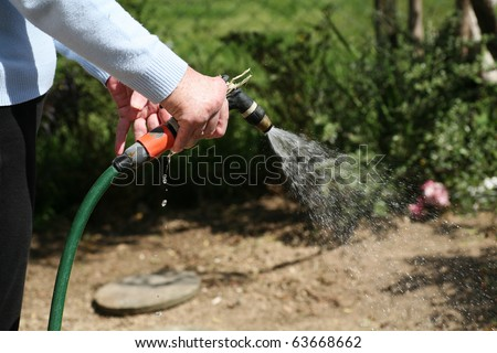 Living with pain series. Senior woman with rheumatoid arthritis watering the garden. - stock photo