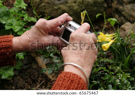 Living with pain series. Woman with rheumatoid arthritis using a digital camera. - stock photo