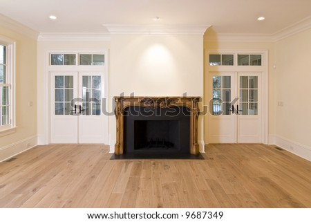 livingroom with intricately carved fireplace and lots of doors and windows - stock photo
