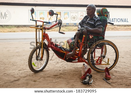 LIVINGSTONE - OCTOBER 14 2013: Local disabled man with an adapted wheelchair sets up successful shoe repair business in Livingstone, Zambia, Africa - stock photo