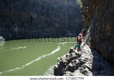 LIVINGSTONE - OCTOBER 01 2013: Tourism brings in huge revenue for Zambia. A canyoner scales the rock formation in the Zambezi river in Livingstone, Zambia, Africa - stock photo